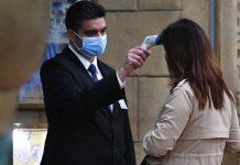 Un hombre coloca un aparato a una mujer para detectar si padece fiebre